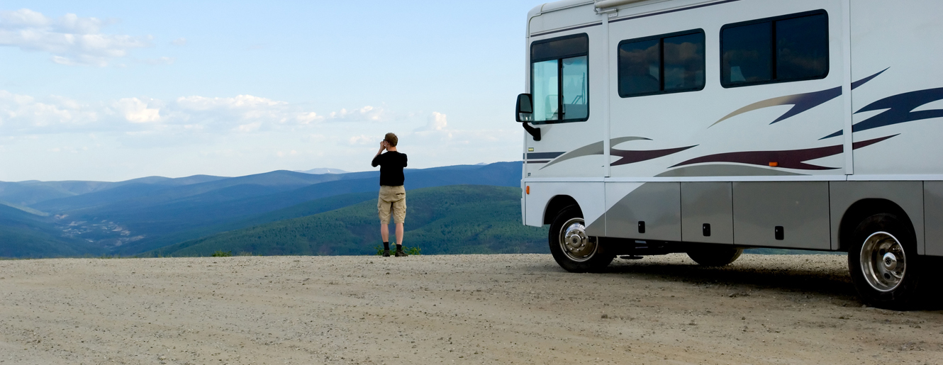 Man viewing mountains outside of his RV Camper.