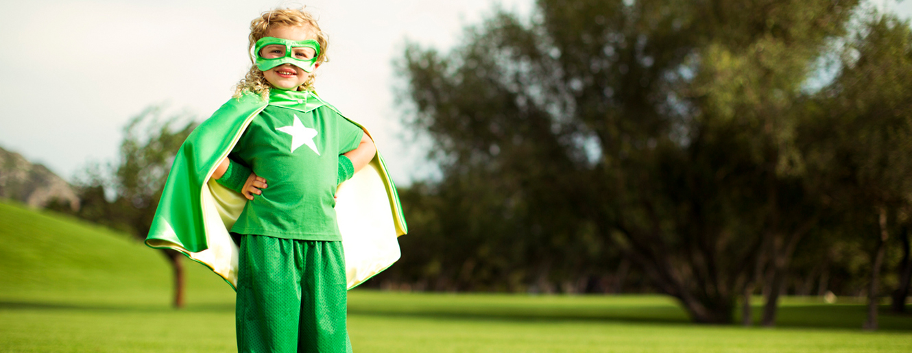 Little girl dressed in green super hero/cape costume